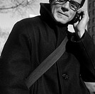 Caucasian Man Wearing A Black Coat And Talking On His Cellphone