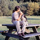 Man Sitting On A Picnic Table And Getting A Kiss From His Dog