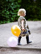 Scandinavia, Sweden, Stockholm, Girl walking with holding balloons