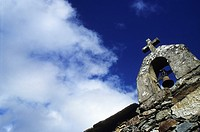 Detail from a bell and a cross, with a strong blue sky and some clouds in background, Aldeia da Pena, Portugal