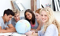 Teenagers in a library working with a terrestrial globe and taking notes