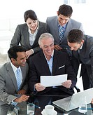 Senior manager showing a document to his team in a meeting