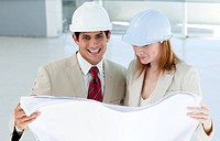 Two smiling engineers studying blueprints in a building site