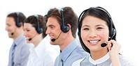 Portrait of smiling customer service agents working in a call center against a white background