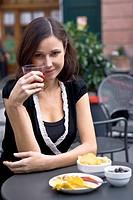 ragazza beve un aperitivo seduta al tavolo di un bar