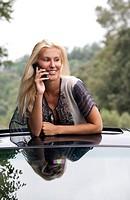 donna bionda con telefonino si affaccia dal tetto apribile di un´auto