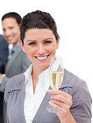 Charming businesswoman toasting with Champagne in front of her team