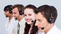 Smiling young woman working in a call center with her colleagues