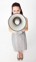 High angle of a beautiful businesswoman shouting through a megaphone