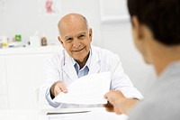 Doctor handing document to patient