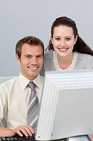 Smiling businesswoman helping her colleague at a computer