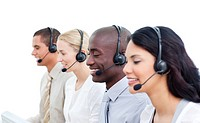 Positive business team working in a call center against a white background