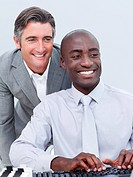 Two cheerful businessman working at a computer in the office