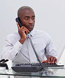 Afro_American businessman talking on phone in the office