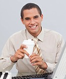 Attractive businessman drinking coffee in the office