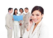 Portrait of a brunette businesswoman on phone with her team on the background
