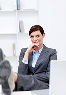 Satisfied Businesswoman sitting in office with feet on desk against white background