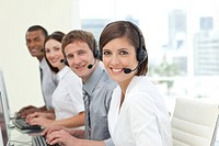 Happy co_workers with headsets on working in call center Business concept
