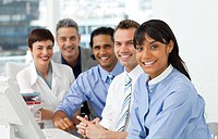 A business group showing diversity looking at the camera in the office
