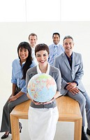 Multi_ethnic business people holding a terrestrial globe in the office
