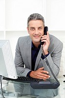 Self_assured businessman on phone at his desk in the office