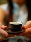 Close_up of a person's hand holding a cup of tea with a saucer