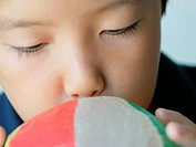 Close_up of a boy blowing a paper balloon