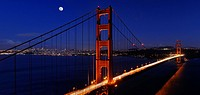 Panorama of Golden Gate Bridge and San Francisco skyline at night with rising moon