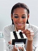 Positive businesswoman consulting a business card holder in the office