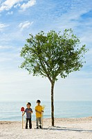 Ecology concept, boys with gardening tools standing by tree growing on beach
