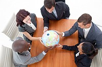 High Angle of business people holding a globe in a meeting Global business