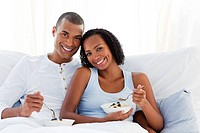 Romantic couple having breakfast lying on their bed