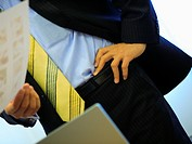 Mid section view of a businessman standing with his hand on his hip and holding a paper