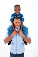 Close_up of a father giving son piggyback ride against white background
