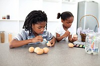 Concentrated Afro_american siblings painting eggs in the kitchen