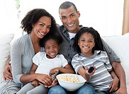 Afro_American family watching television and eating popcorn at home