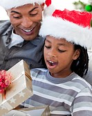 Portrait of a happy Afro_American father and son opening a Christmas gift