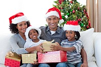 Smiling Afro_American family sharing Christmas presents on the sofa