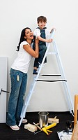 Cute little boy climbing a ladder while renovating a room
