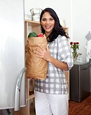 Brunette woman unpacking grocery bag in the kitchen