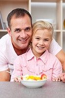 Happy little girl eating fruit with her father in the kitchen