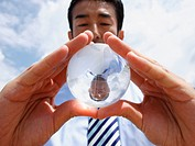 Low angle view of a businessman holding a transparent globe