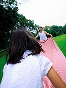 Rear view of a girl holding a sheet with her mother in a park