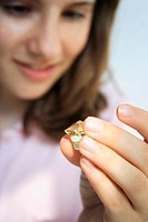Close_up of a teenage girl holding a gem stone and smiling