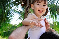 Close_up of a man holding her daughter in air