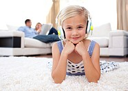 Smiling little girl listening music lying on the floor in the living_room