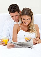 Lovers reading a newspaper and drinking orange juice lying on their bed