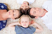 Relaxed family lying in circle on the wall_to_wall carpet at home