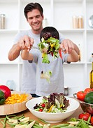 Happy father and his son preparing a salad in the kitchen