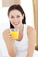Smiling woman drinking orange juice sitting on her bed